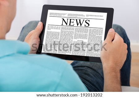 Closeup of mid adult man reading newspaper on digital tablet at home