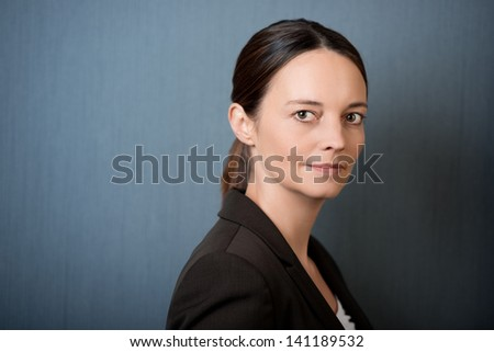 closeup of mid aged thoughtful businesswoman against blue wall - stock photo
