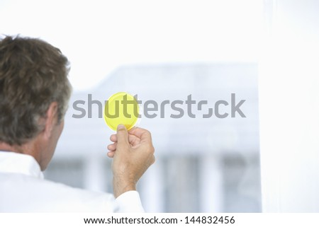 Closeup of middle aged scientist examining yellow petri dish