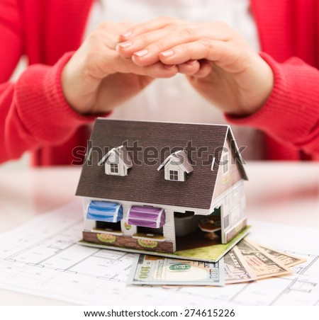 Closeup of miniature house standing on dollars banknotes at real estate agent desk in the office. Shallow depth of field. - stock photo