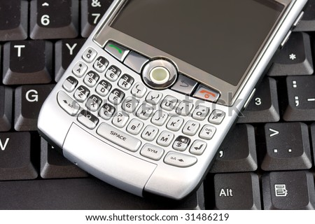 Closeup of mobile phone with laptop keyboard as background