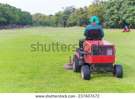 Closeup of mower cutting the grass in public park. - stock photo
