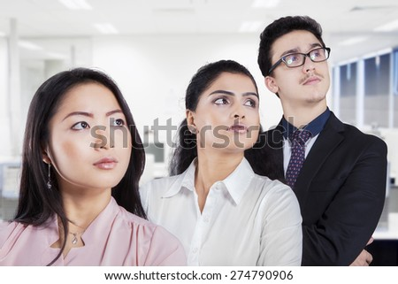 Closeup of multi ethnic businesspeople standing in the office and looking at copyspace - stock photo
