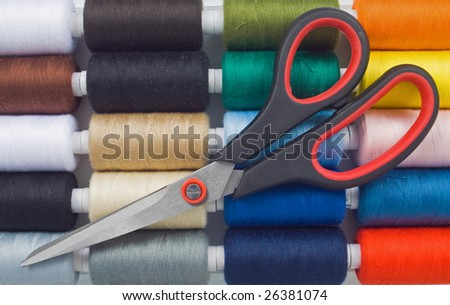 closeup of multicolored sewing spools and scissors - stock photo