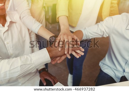 Closeup of multiethnic group of young people standing and joining hands
