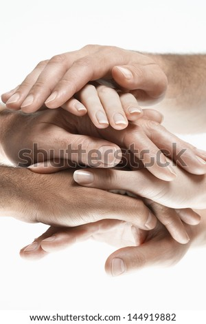 Closeup of multiethnic men and women piling hands on top of each other against white background - stock photo