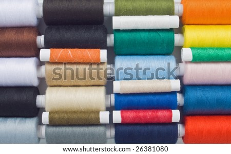 closeup of muticolored sewing spools - stock photo