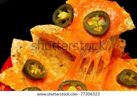 Closeup of nachos with jalapeno pepper slices.  Isolated on black background. - stock photo