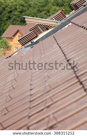 Closeup of new roof with skylight and natural red tile - stock photo