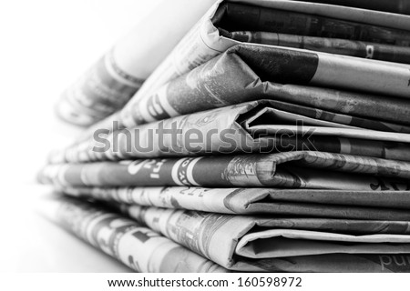 Closeup of newspapers on plain background - stock photo