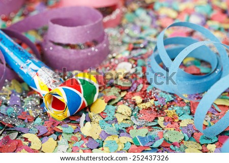 closeup of noisemaker on confetti and streamers - stock photo