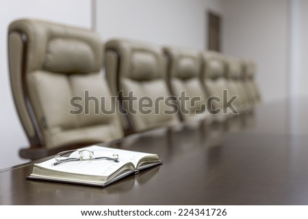 Closeup of  notebook on table in empty corporate conference room before business meeting in office