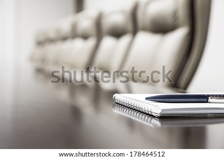 Closeup of notepad for agenda kept on table in empty corporate conference room before business meeting - stock photo