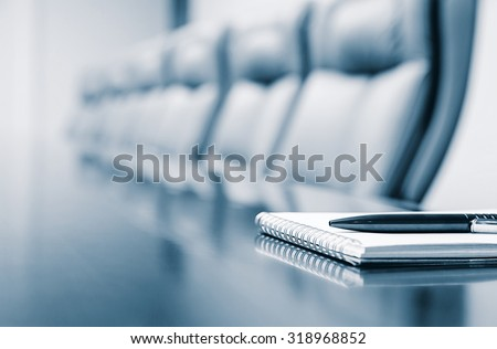 Closeup of notepad for agenda kept on table in empty corporate conference room before business meeting in blue tone - stock photo