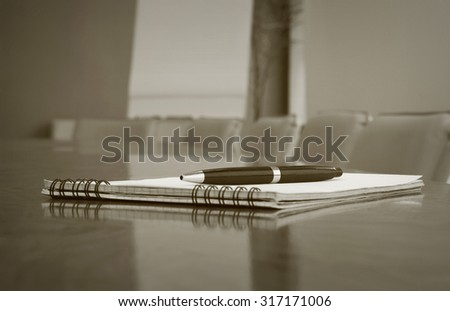 Closeup of notepad on table in empty conference room before business meeting - stock photo