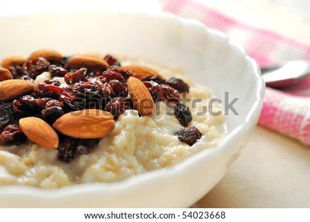 Closeup of nutritious oatmeal topped with raisins and nuts for a healthy breakfast. Also for healthy lifestyle, diet and nutrition, and food and beverage concepts. - stock photo