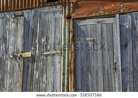 Closeup of old boat shed doors in New Zealand, made of wood and rusty iron