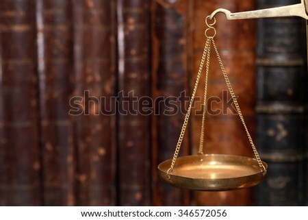 Closeup of old brass weight scales on cover books background
