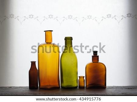 Closeup of old empty glass bottles at windowsill against daylight - stock photo