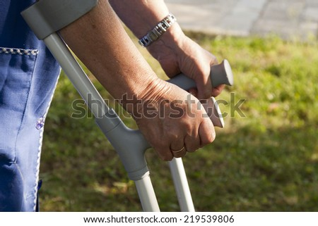 closeup of old hands with crutches - stock photo