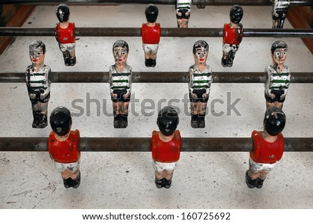 Closeup of old miniature metallic ball players of a football table game. - stock photo