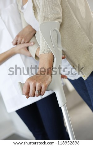 Closeup of old woman's hands leaning on crutches - stock photo
