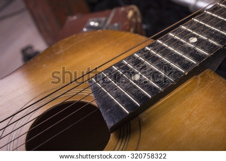 Closeup of one acoustic string light brown color wooden musical instrument of guitar with beautiful shape indoor in studio, horizontal picture