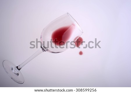 Closeup of one beautiful clear glass goblet with drop of tasty sweet red dessert grape wine with bubbles lying isolated on white studio background, horizontal picture - stock photo