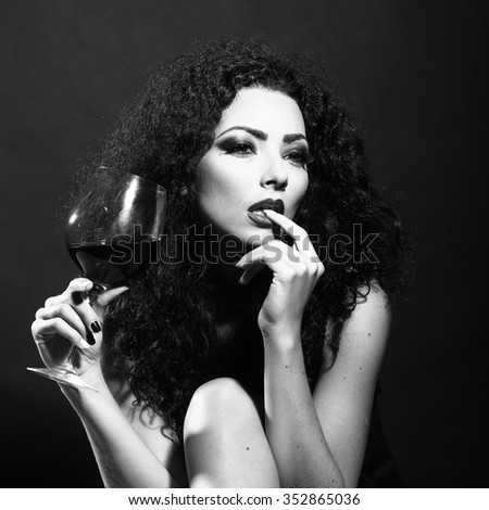 Closeup of one pretty sensual mysterious young brunette sexy woman with long curly hair and bright makeup in dress sitting in studio drinking wine from glass black and white, square picture - stock photo