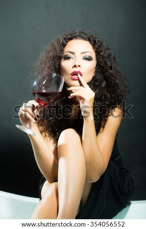 Closeup of one pretty sensual mysterious young brunette sexy woman with long curly hair and bright makeup in dress sitting in studio drinking red wine from glass on black background, vertical picture - stock photo