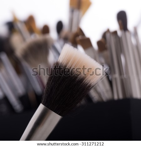 Closeup of one professional natural soft make-up brushes for eyeshadow powder and facial foundation for visagistes brown color and set of tools on blur background, square picture - stock photo