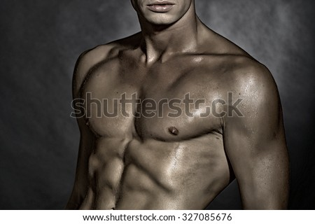 Closeup of one young sexual naked man with beautiful wet muscular strong body and torso standing in studio on grey wall background, horizontal picture - stock photo