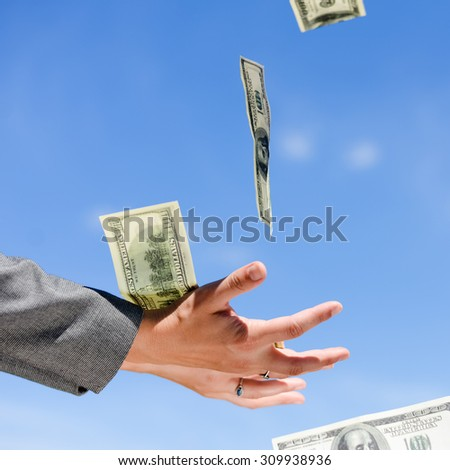 Closeup of open hands trying to catch few flying USD dollar banknotes on blue sky background. - stock photo