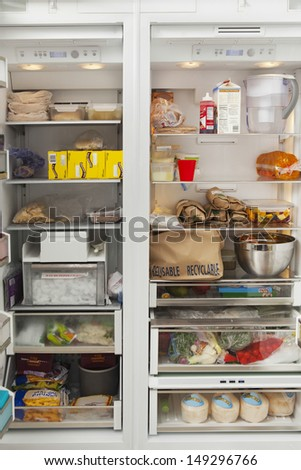 Closeup of open refrigerator with food items in commercial kitchen - stock photo