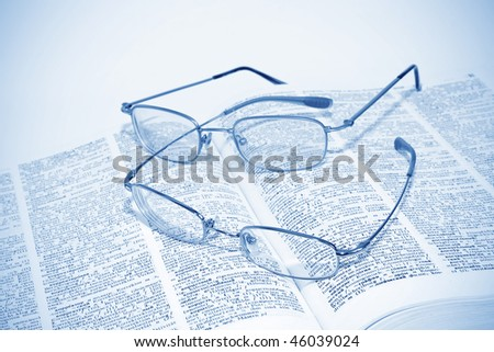 closeup of opened book and glasses - stock photo