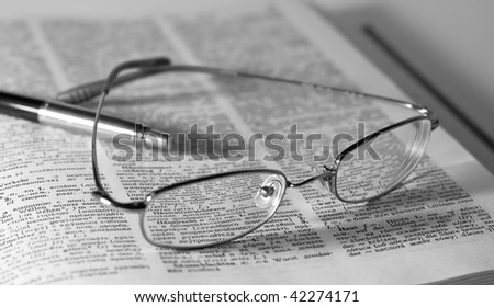 closeup of opened book, glasses and pen