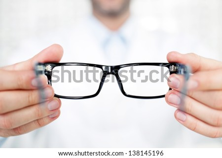 Closeup of optometrist, optician giving glasses  to try - stock photo