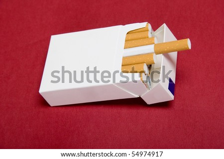 closeup of packet cigarettes on red background - stock photo