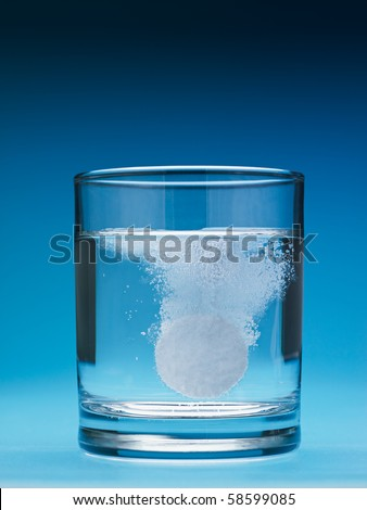 closeup of painkiller tablet in glass of water. Vertical shape, copy space - stock photo