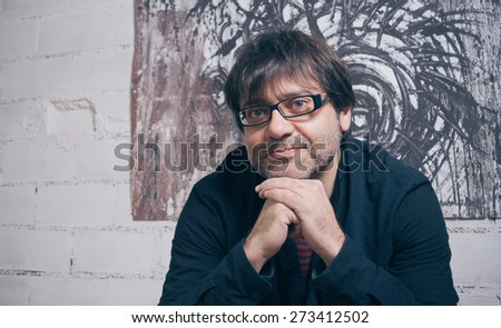 Closeup of painter artist posing in front of one modern artwork in his studio - stock photo