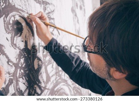 Closeup of painter artist working in a modern abstract oil canvas in his studio - stock photo