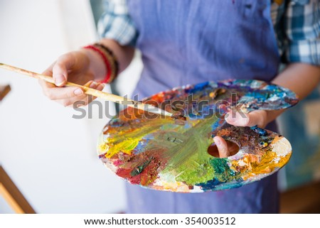 Closeup of palette with mixed paints holded by hands of young woman artist