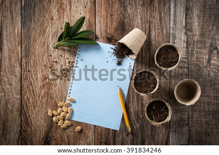 Closeup of peat planting pots filled with soil and seeds with sheet of blank paper to write shot on rustic wooden background. Gardening and planting seedlings, spring is here concept. Copyspace. - stock photo