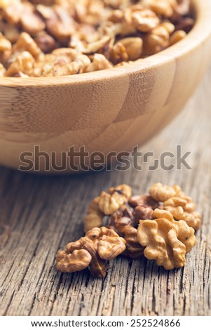 closeup of peeled walnuts on wooden table - stock photo