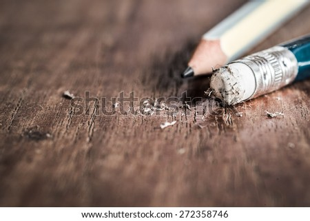 Closeup of pencil eraser on wooden table, soft focus. Mistake erase concept. - stock photo