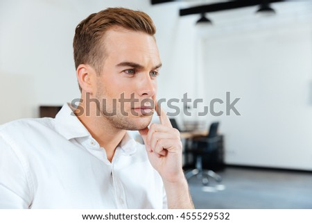 Closeup of pensive young businessman sitting and thinking in office - stock photo