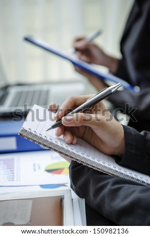 Closeup of people hands taking note - stock photo