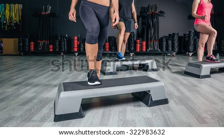 Closeup of people legs over step boards training in aerobic class on a fitness center. Sport and health concept. - stock photo