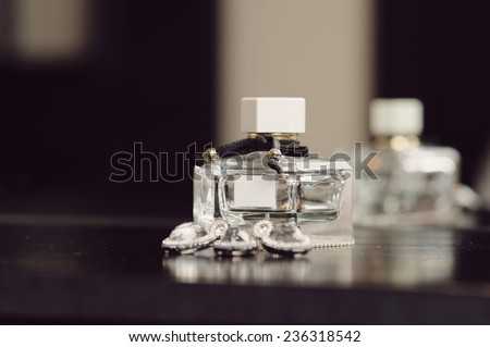 closeup of perfume bottle and jewelry set - stock photo