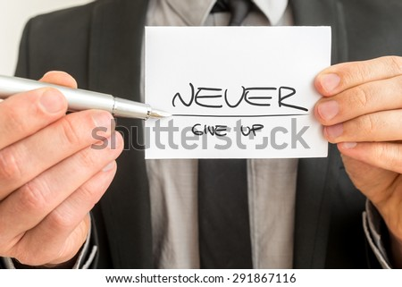 Closeup of personal motivator holding up a white card with a motivational message Never give up. - stock photo